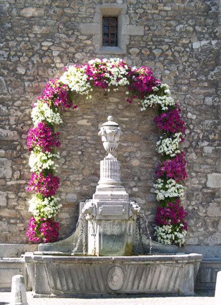Каменный фонтан, украшенный гирляндой цветов / Фото из Швейцарии