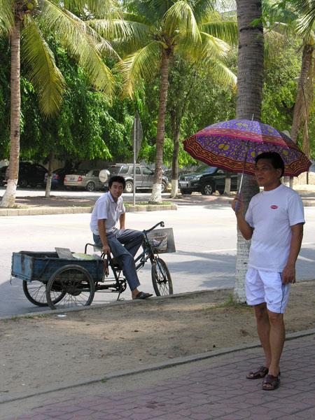 Китаец под зонтиком - типичная картина на Хайнане / Фото из Китая