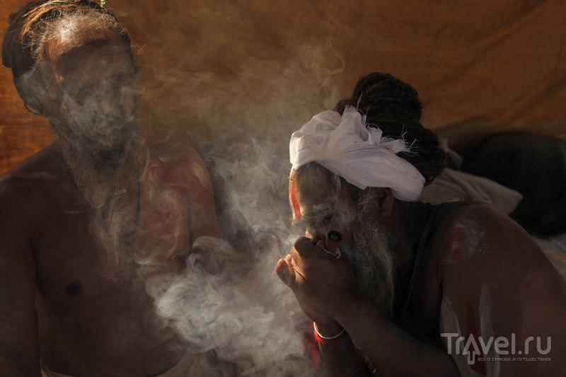 Святой человек курит марихуану в Сангам / Индия