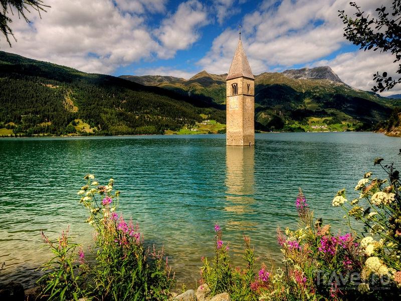 Колокольня, возвышающаяся над озером Резия на севере Италии / Италия