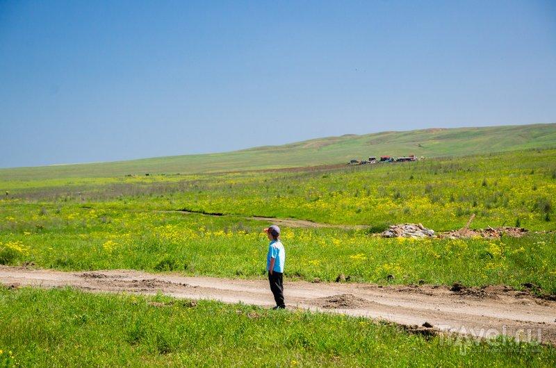 Здесь, прямо у знака на въезде в Тамань, начинается дорога к памятнику природы Карабетова сопка - самому высокому из действующих вулканов Тамани, гряда сопок видна справа на горизонте