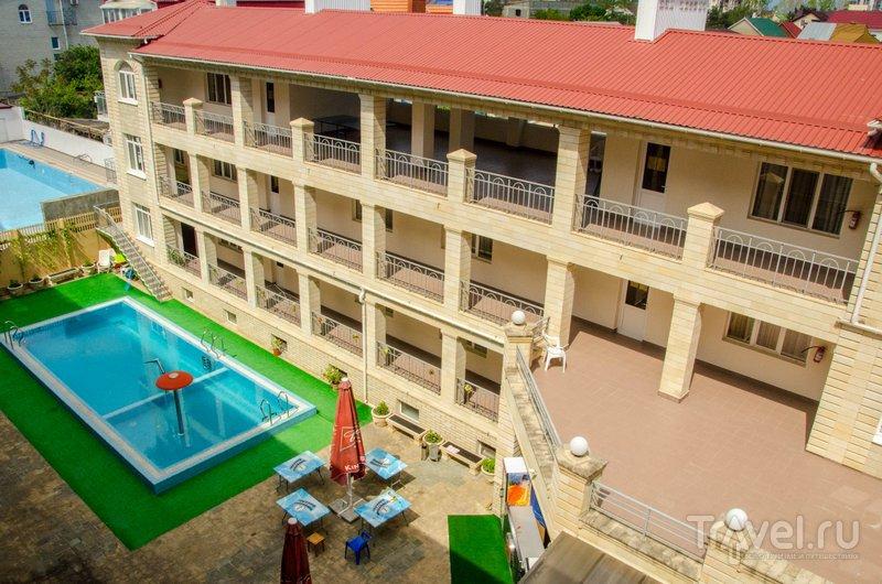 Вид с одного из балконов во двор гостиницы на бассейн и летнее кафе