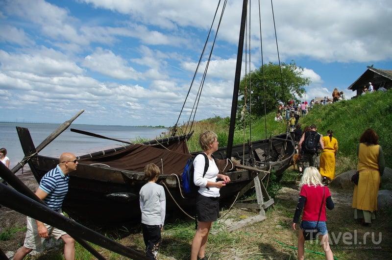 Туристы осматривают военный корабль викингов - драккар
